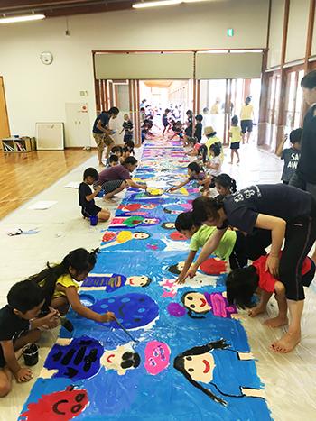 幼稚園児とステージバックの大型絵画制作